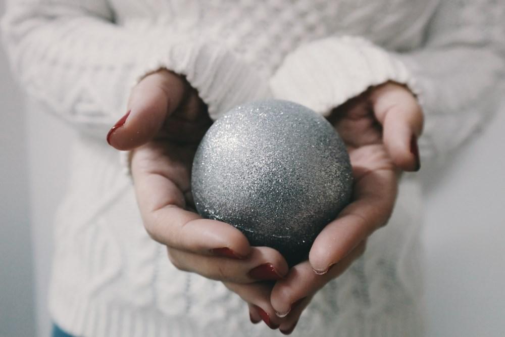 Mani con pallina albero di Natale